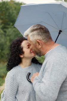 Cerca de una pareja romántica besándose en un parque de otoño. hombre y mujer vistiendo suéteres azules. la mujer es morena y el hombre es gris.