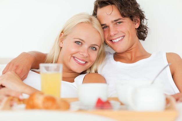 Cerca de una pareja sonriente desayunando
