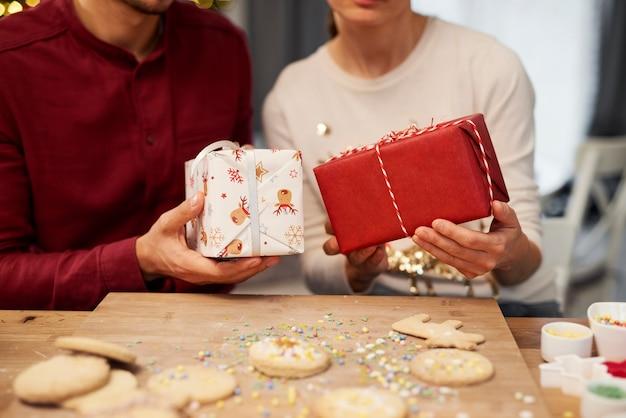 Cerca de pareja sosteniendo regalos de navidad con galletas