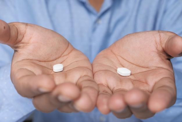 Cerca de pastillas blancas en la palma de la mano