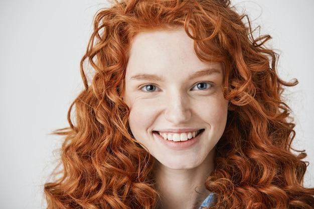Cerca de pelirroja hermosa mujer con pecas sonriendo.