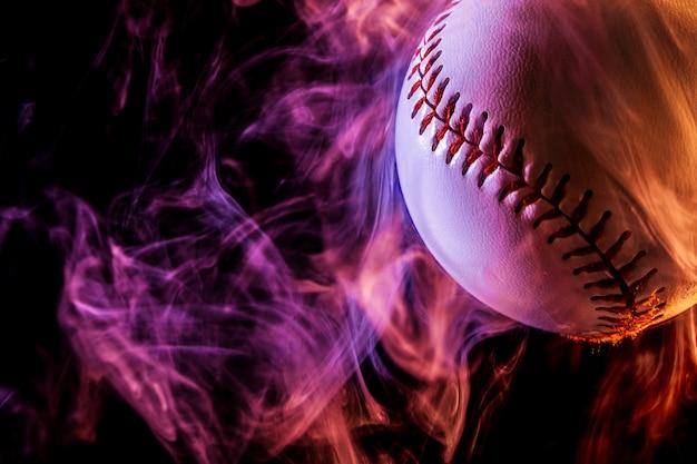 Cerca de una pelota de béisbol blanca en humo rojo