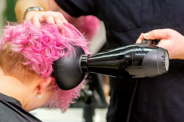 Cerca de peluquería secando el pelo corto de color rosa o rojo con un secador de pelo en un salón de belleza