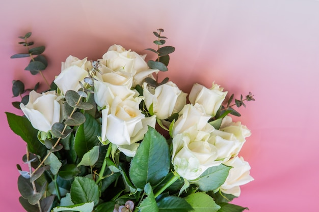 Cerca de un pequeño ramo de flores rosas blancas sobre un fondo degradado rosa con espacio de copia