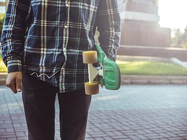 Cerca de persona en la calle de verano con penny skate en un día soleado