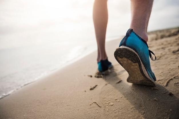 Cerca de la persona joven en forma de jogging por el mar