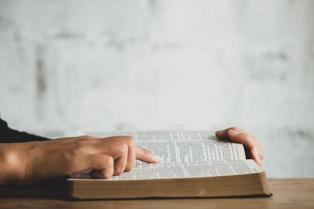 De cerca a la persona que lee la biblia