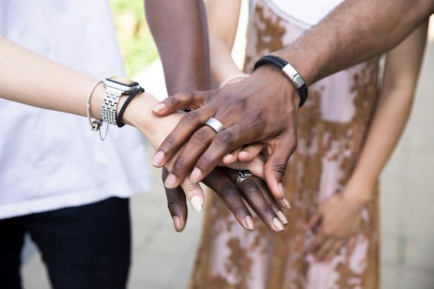 Cerca de personas interraciales tomados de la mano