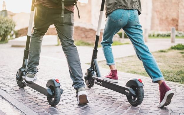 Cerca de personas pareja usando scooter eléctrico en el parque de la ciudad