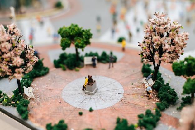 Cerca de personas pequeñas o personas modelo caminando en el parque.