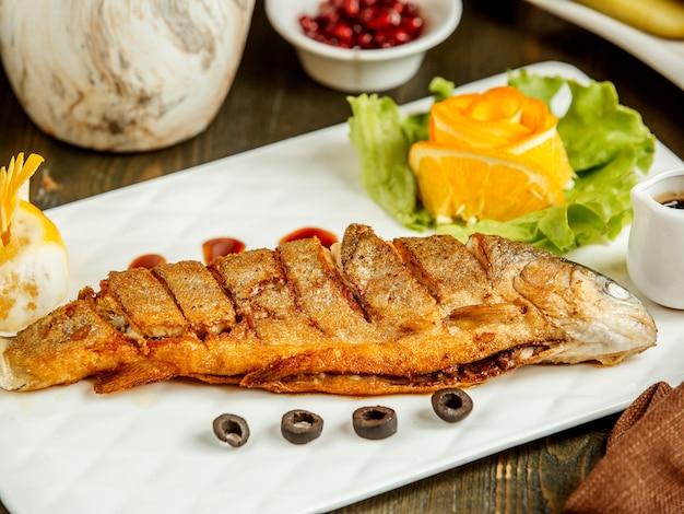 Cerca de pescado entero frito servido con salsa