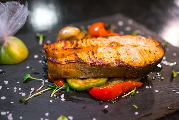 Cerca de pescado a la plancha decorado con verduras.