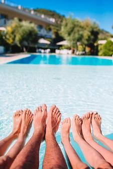 Cerca de las piernas de cuatro personas al lado de la piscina