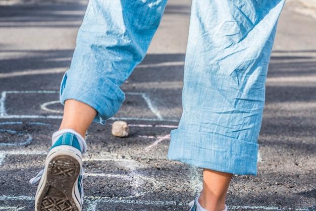 Cerca de las piernas de una mujer saltando y jugando a la rayuela - retrato de dama divirtiéndose saltando sobre el asfalto