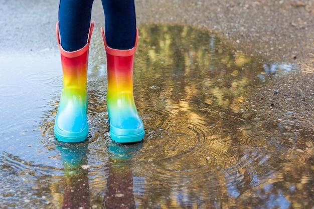 Cerca de las piernas de la niña niño con botas de goma del arco iris saltar en el charco en un paseo de otoño.