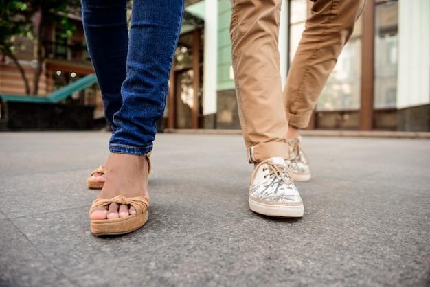 Cerca de las piernas de la pareja en keds caminando por la calle.