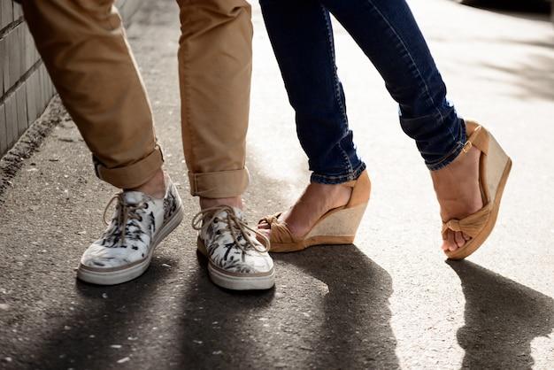 Cerca de las piernas de la pareja en keds de pie en la calle.