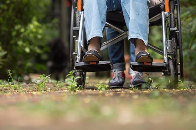 Cerca de los pies de la anciana en silla de ruedas caminando con el cuidador