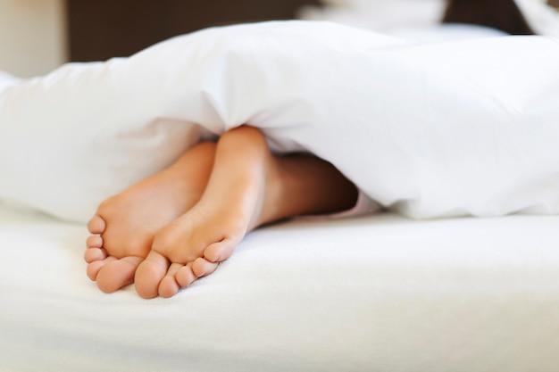 Cerca de pies femeninos en la cama