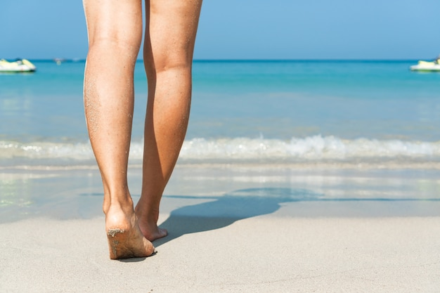 Cerca de pies femeninos caminando en la playa de arena blanca