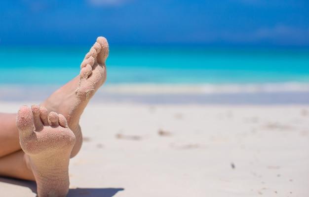Cerca de pies femeninos en la playa de arena blanca