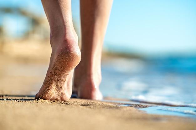 Cerca de pies de mujer caminando descalzo sobre la arena dejando huellas en la playa dorada