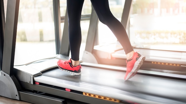 Cerca de los pies de las piernas musculares de la mujer que se ejecutan en la cinta de entrenamiento en el gimnasio de fitness