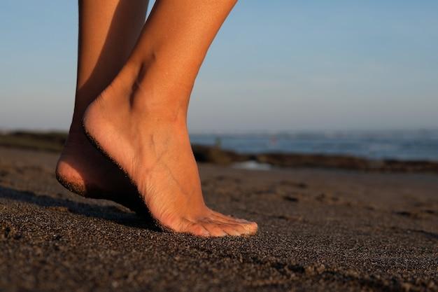 De cerca. pies sobre arena negra. bali
