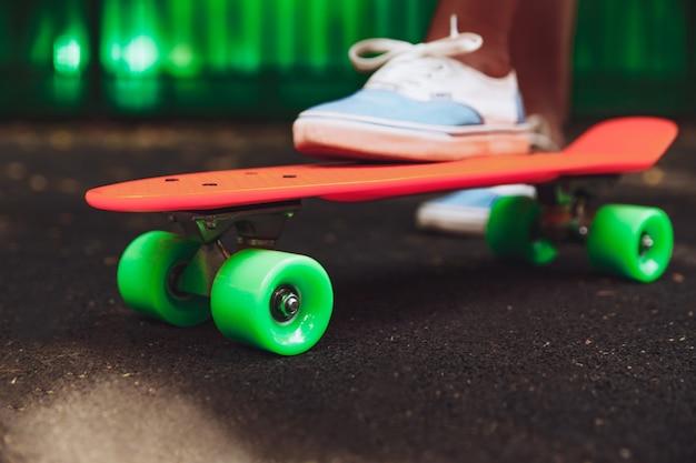 Cerca de los pies de las zapatillas de niña monta en patineta centavo naranja sobre asfalto
