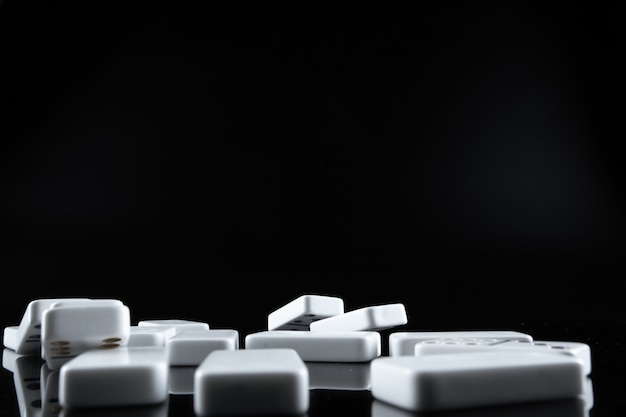 Cerca de piezas de dominó sobre fondo negro