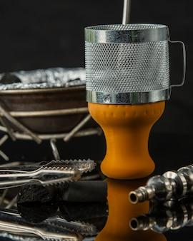 Cerca de piezas de shisha naranja carbón y pipa