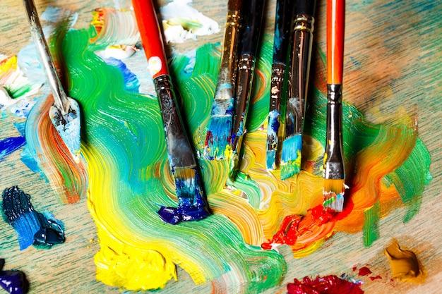 Cerca de pinturas al óleo y pinceles en la paleta