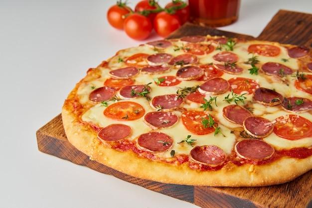 Cerca de pizza de pepperoni italiana casera caliente con salami, mozzarella en mesa blanca, cena rústica con salchichas y tomates, vista lateral.