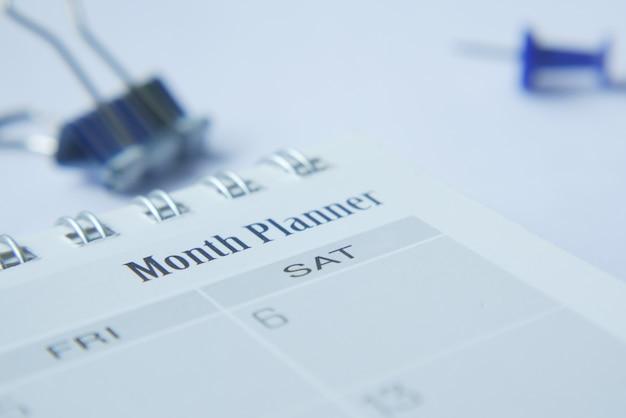 Cerca del planificador mensual y el bloc de notas en la mesa