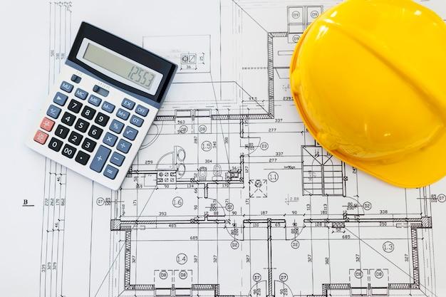 Cerca de planos de casa con casco amarillo