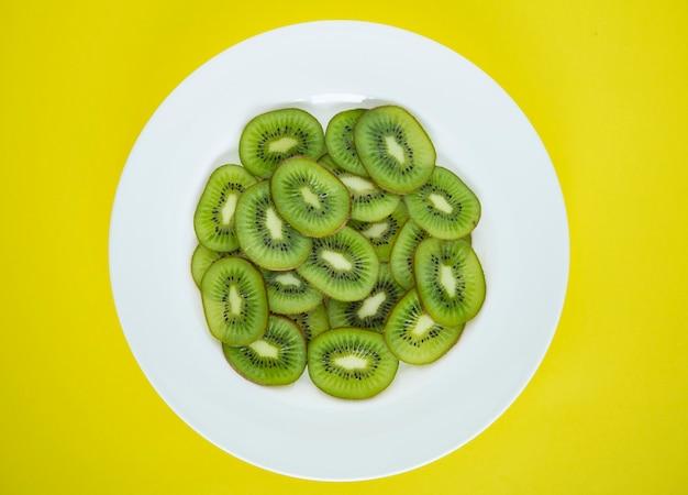 Cerca de un plato de rodajas de fruta kiwi verde