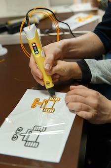 Cerca de la pluma de impresión 3d siendo utilizado por el niño.
