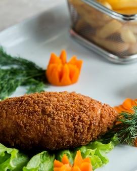 Cerca de pollo empanado decorado con flores de zanahoria