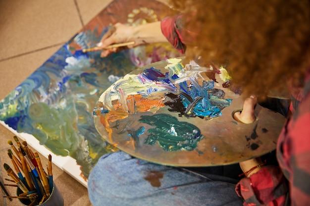 Cerca del proceso un artista está dibujando una pintura