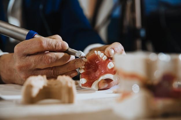 De cerca los procesos del técnico dental de construir una mandíbula
