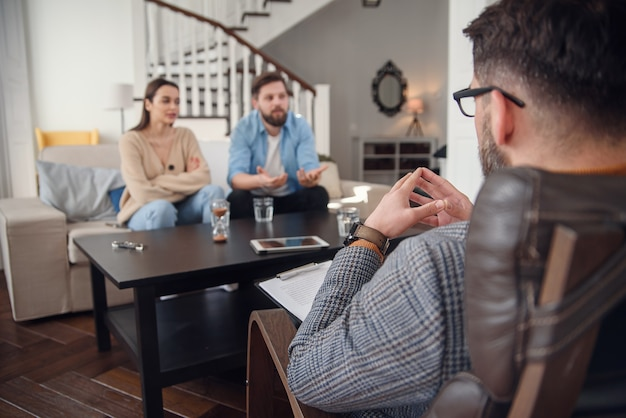 Cerca del psicólogo masculino se sienta en la silla y escucha deprimida joven pareja en la oficina con estilo acogedor. enfoque selectivo.