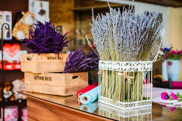 Cerca del ramo de flores de lavanda en una jaula de metal y caja de madera
