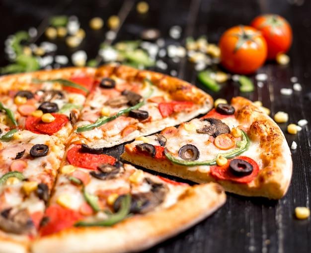 Cerca de rebanadas de pizza de pepperoni con salchichas champiñones oliva pimiento y queso
