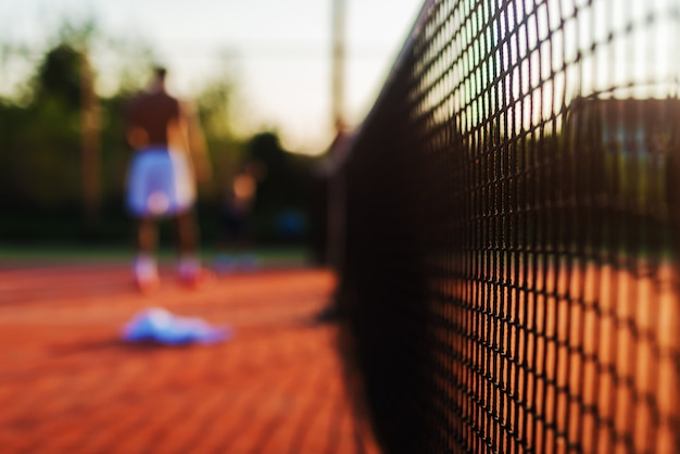 Cerca de la red de tenis enfocado con la figura borrosa de un hombre