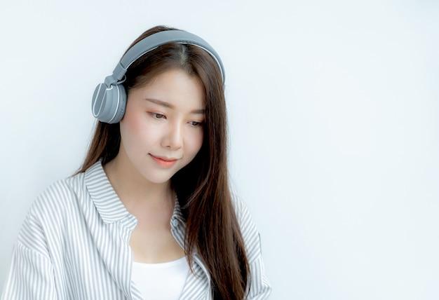 Cerca del retrato de mujer asiática con auriculares mirando al frente.