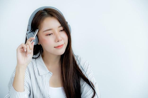 Cerca del retrato de mujer asiática con auriculares sosteniendo una pluma mirando al frente.