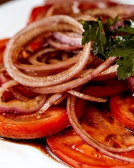 Cerca de rodajas de tomate cubiertas con aros de cebolla roja en salsa con perejil