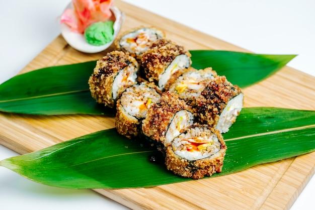 Cerca de rollos de sushi calientes servidos con jengibre y wasabi en tablero de madera