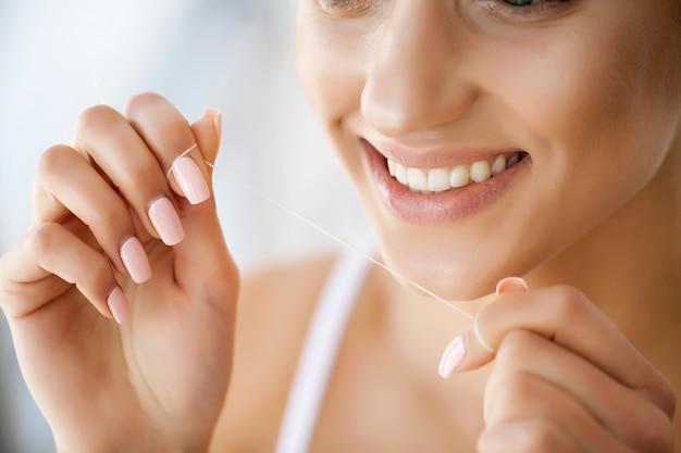 Cerca de rostro femenino con una sonrisa perfecta. niña limpia dientes con hilo especial