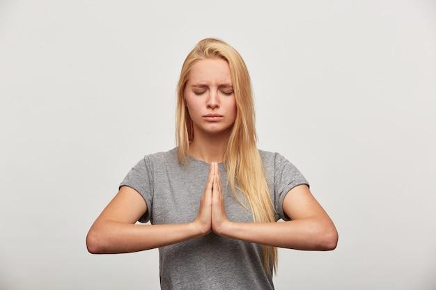 Cerca de rubia meditando, se concentra en algo, practicando ejercicios de yoga de respiración